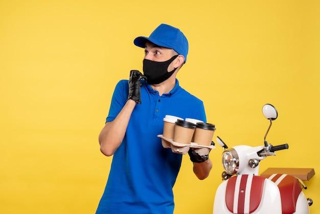 Vooraanzicht mannelijke koerier in zwart masker met koffie op gele baan covid-pandemische uniforme werkdienst