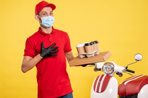 Vooraanzicht mannelijke koerier met bezorgkoffie en voedseldoos op lichtgele dienstbaan kleur covid-virus pandemie werkuniform