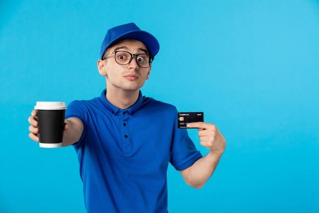 Vooraanzicht mannelijke koerier met koffie en creditcard op blauw