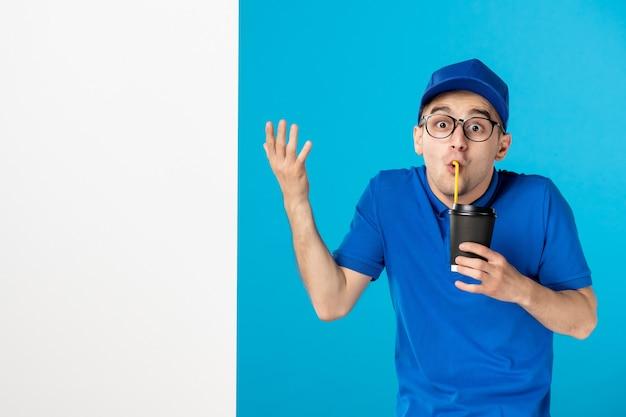 Vooraanzicht mannelijke koerier met koffie op blauw