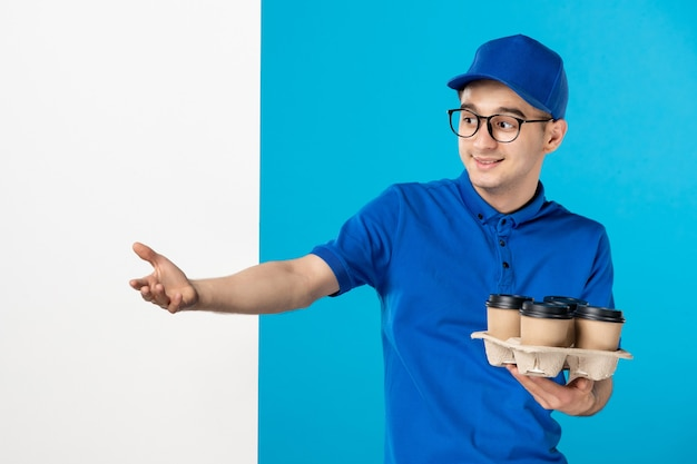 Vooraanzicht mannelijke koerier met koffiekopjes op blauw