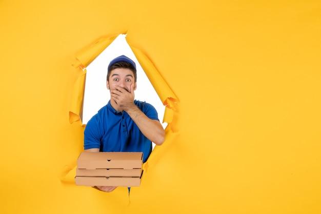 Vooraanzicht mannelijke koerier met pizzadozen op gele ruimte