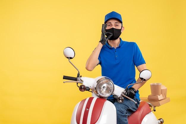 Vooraanzicht mannelijke koerier op fiets in masker op een gele de baanpandemische levering van de werkdienst covid-uniforme
