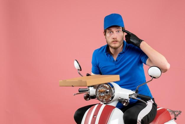 Vooraanzicht mannelijke koerier zittend op de fiets en pizzadoos op het roze te houden