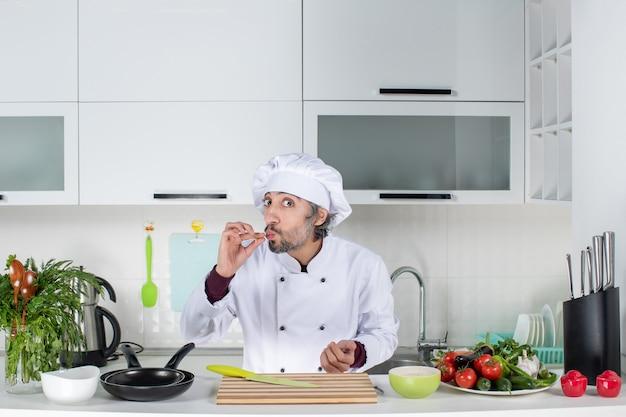 Vooraanzicht mannelijke kok in uniform die chef-kok kus in keuken maakt