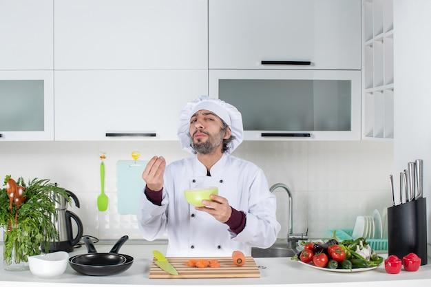 Vooraanzicht mannelijke kok in uniform die een smakelijk bord maakt met een kom in de keuken