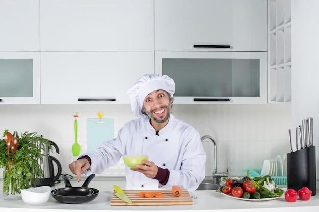 Vooraanzicht mannelijke kok in uniform die kom omhoog houdt wijzend op pannen in de keuken