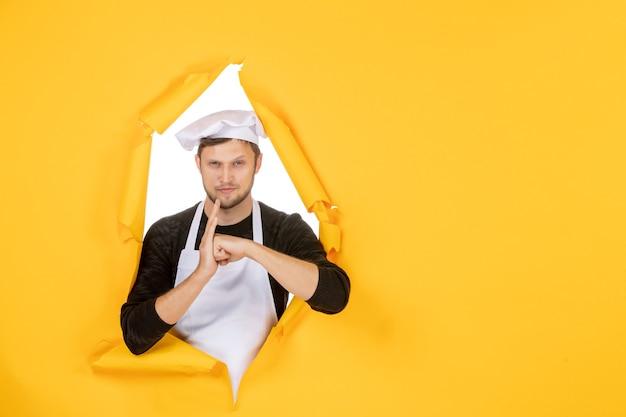 Vooraanzicht mannelijke kok in witte cape en pet op gele gescheurde baan kleur wit foto keuken eten man keuken