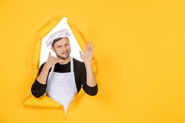 Vooraanzicht mannelijke kok in witte cape en pet op gele gescheurde baan kleur witte foto keuken eten keuken