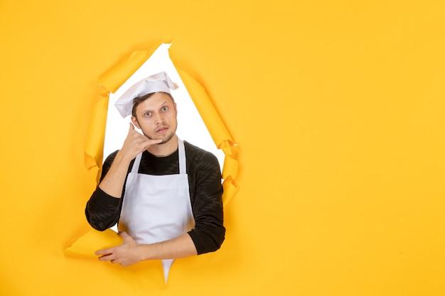 Vooraanzicht mannelijke kok in witte cape en pet op gele gescheurde baan kleur witte foto keuken man keuken