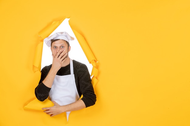 Vooraanzicht mannelijke kok in witte cape en pet op gele gescheurde baan kleur witte keuken eten keuken foto