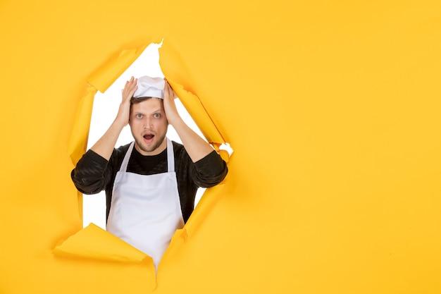 Vooraanzicht mannelijke kok in witte cape en pet op gele gescheurde baan kleur witte keuken eten man keuken foto's
