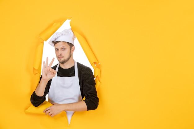 Vooraanzicht mannelijke kok in witte cape en pet op gele gescheurde baan kleur witte keuken man keuken foto