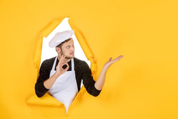 Vooraanzicht mannelijke kok in witte cape en pet op gele gescheurde baan kleurenfoto keuken eten keuken