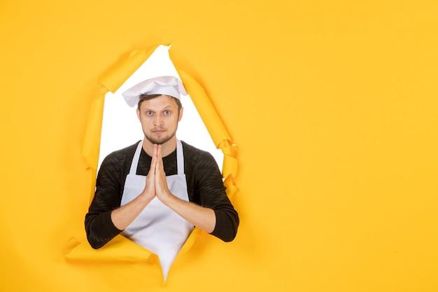 Vooraanzicht mannelijke kok in witte cape en pet op gele gescheurde baan kleurenfoto keuken eten man
