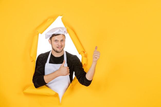 Vooraanzicht mannelijke kok in witte cape en pet op gele gescheurde baan kleurenfoto voedsel man keuken