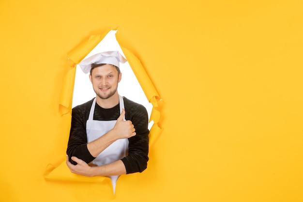 Vooraanzicht mannelijke kok in witte cape en pet op gele gescheurde keuken kleurenfoto baan keuken eten man