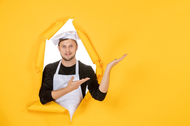 Vooraanzicht mannelijke kok in witte cape en pet op gele gescheurde keuken kleurenfoto baan keuken eten