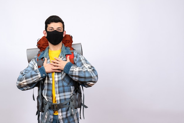 Vooraanzicht mannelijke reiziger met rugzak en masker handen op zijn borst zetten