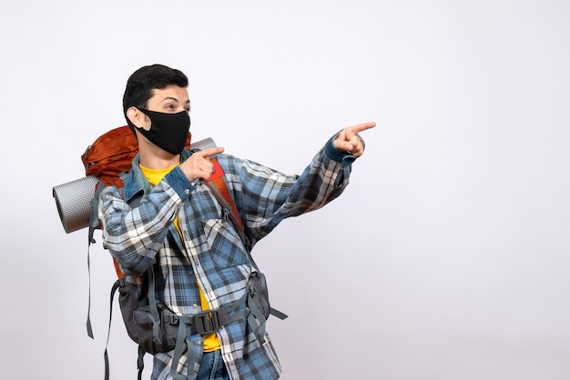 Vooraanzicht mannelijke reiziger met rugzak en masker naar iets wijzend