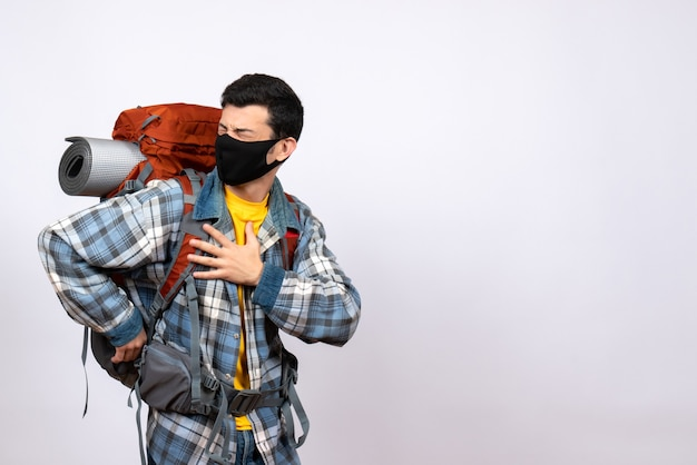 Vooraanzicht mannelijke reiziger met rugzak en masker op de borst met pijn