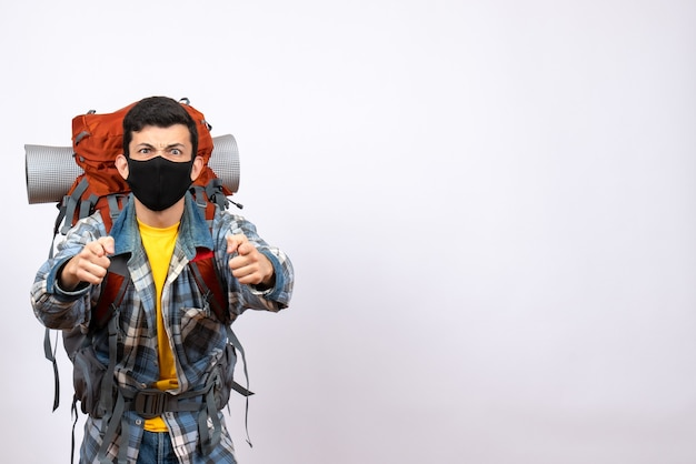 Vooraanzicht mannelijke reiziger met rugzak en masker wijzend op camera