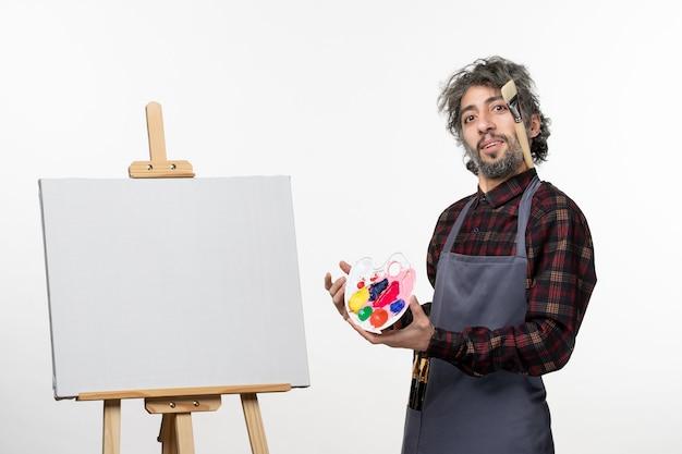 Vooraanzicht mannelijke schilder die verf vasthoudt en zich voorbereidt om op een witte muur te tekenen