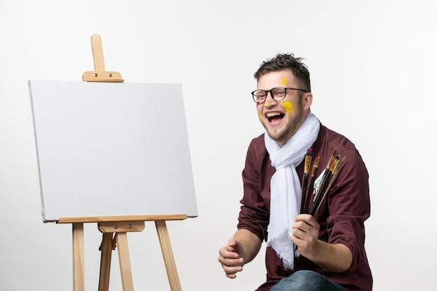 Vooraanzicht mannelijke schilder die verfborstels op witte muur houdt