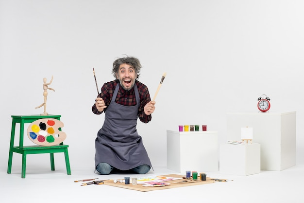Vooraanzicht mannelijke schilder met kwasten voor het tekenen op de witte achtergrond kunst foto kunstenaar tekening schilderij kleur