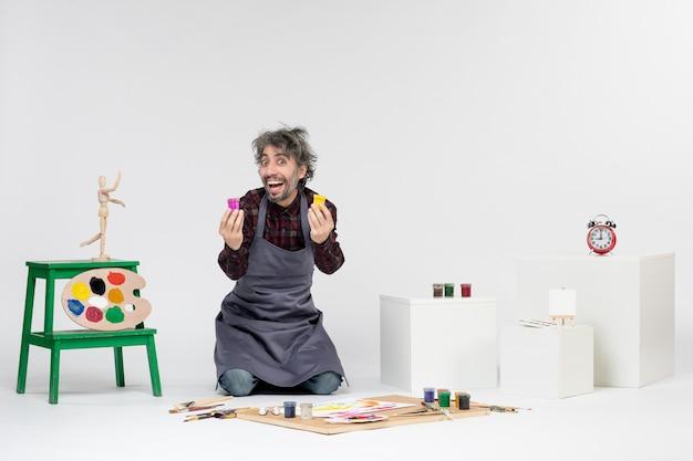 Vooraanzicht mannelijke schilder met verf voor het tekenen in kleine blikjes op een witte achtergrond kleur tekening foto kunstenaar schilderij kunst