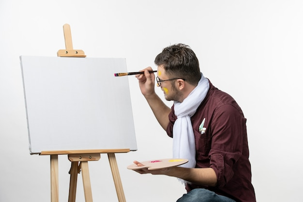 Vooraanzicht mannelijke schilder tekenen op ezel met kwast en verf op witte muur