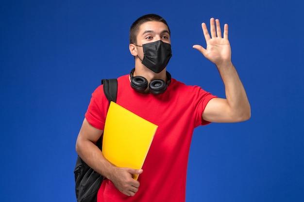 Vooraanzicht mannelijke student in rode t-shirt dragen masker met rugzak gele bestand op de blauwe achtergrond te houden.