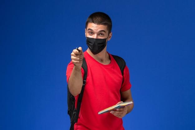 Vooraanzicht mannelijke student in rode t-shirt dragen rugzak in zwarte steriele masker met pen en voorbeeldenboek op de blauwe achtergrond.