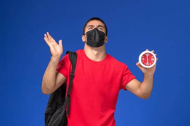 Vooraanzicht mannelijke student in rode t-shirt dragen rugzak met masker houden klokken op de blauwe achtergrond.