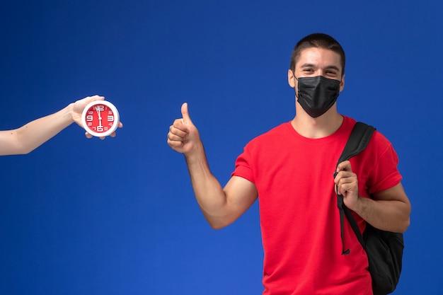 Vooraanzicht mannelijke student in rode t-shirt dragen rugzak met masker poseren op het blauwe bureau.