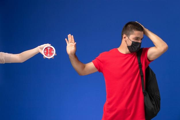 Vooraanzicht mannelijke student in rood t-shirt dragen rugzak met masker poseren op de blauwe achtergrond.