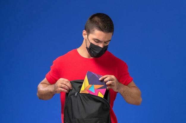 Vooraanzicht mannelijke student in rood t-shirt masker dragen en houdt zijn rugzak op de blauwe achtergrond.
