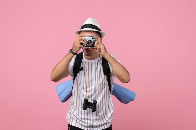 Vooraanzicht mannelijke toerist die een foto maakt met camera op de roze muur toeristische emoties kleur