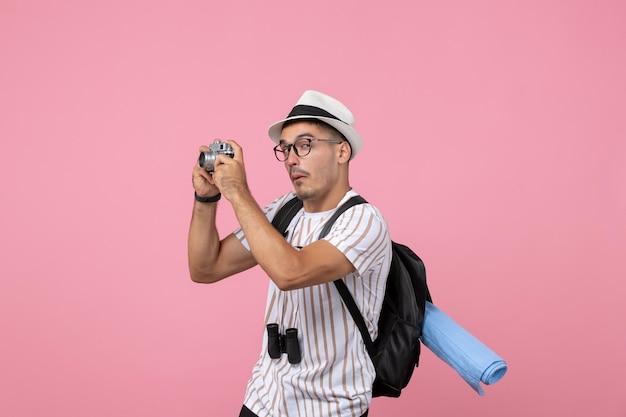 Vooraanzicht mannelijke toerist die foto's maakt met camera op roze muuremoties toeristische kleur