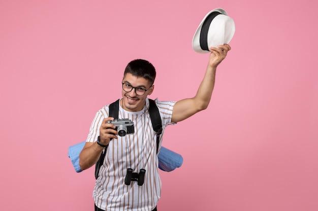 Vooraanzicht mannelijke toerist met camera die zijn hoed afdoet op roze muur emotie kleur toerist