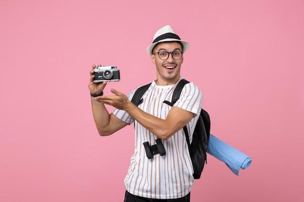 Vooraanzicht mannelijke toerist met camera op de roze muur emotie toeristische kleur