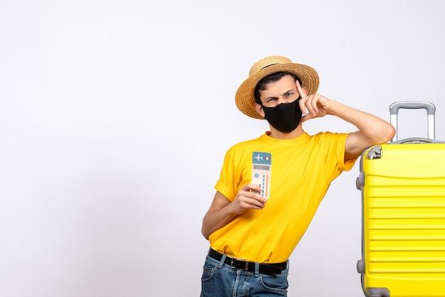 Vooraanzicht mannelijke toerist met strohoed die zich dichtbij het gele reiskaartje van de kofferholding bevindt