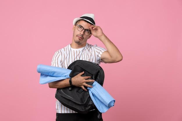 Vooraanzicht mannelijke toerist met zijn rugzak op lichtroze muur emotie kleur toerist
