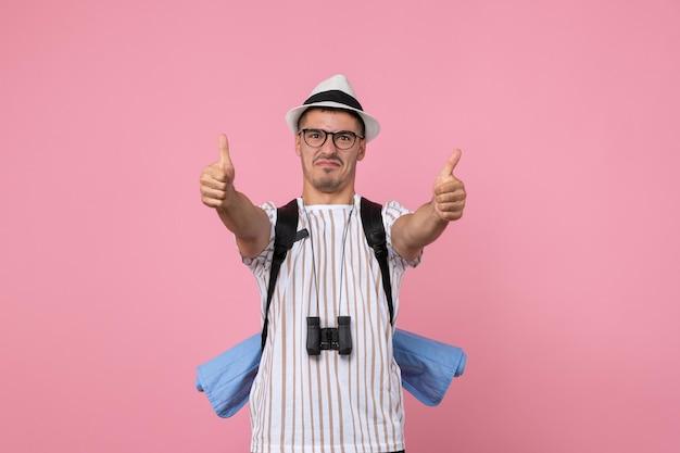 Vooraanzicht mannelijke toerist met zijn rugzak op roze muurkleur emotie toerist
