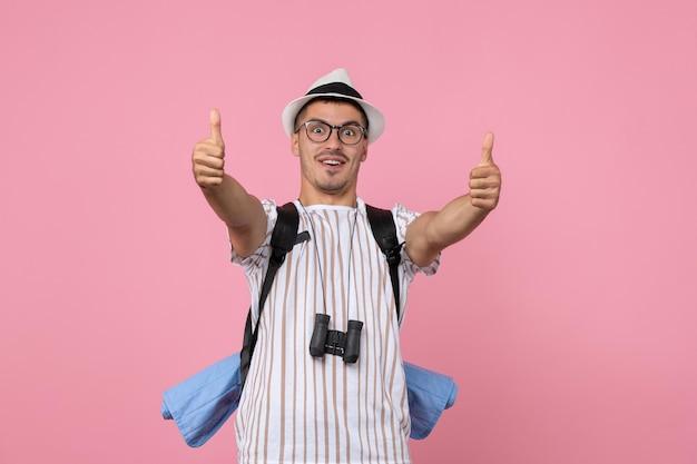 Vooraanzicht mannelijke toerist poseren met rugzak op de roze muur kleur emotie toerist