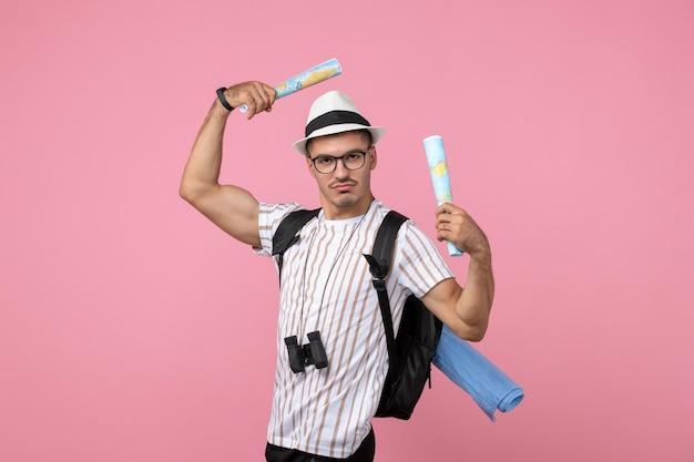 Vooraanzicht mannelijke toerist wandelen met kaarten op de roze muur toeristische emotie kleur