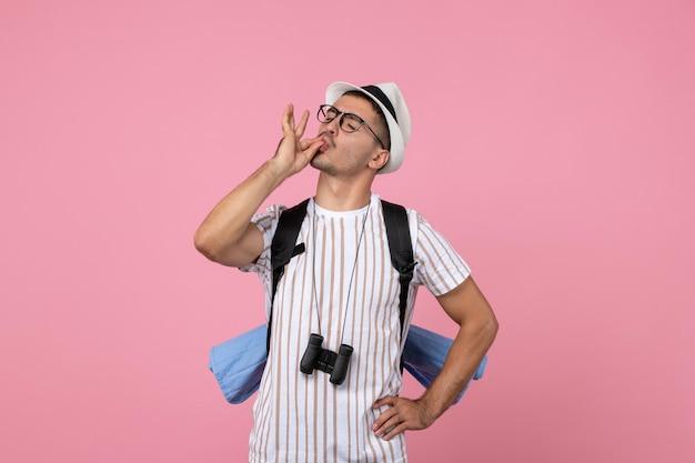 Vooraanzicht mannelijke toerist wandelen met rugzak op de roze muur kleur emotie toerist
