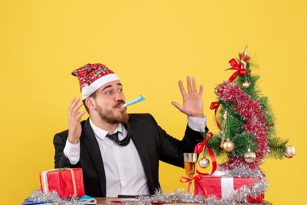 Vooraanzicht mannelijke werknemer achter zijn tafel met cadeautjes op een geel