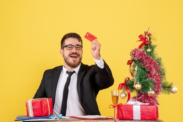 Vooraanzicht mannelijke werknemer achter zijn werkplek met bankkaart op geel