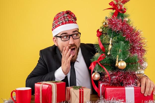 Vooraanzicht mannelijke werknemer achter zijn werkplek met cadeautjes op geel